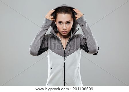 Attractive fitness woman in earphones putting on her hood and looking at camera while standing isolated over gray background