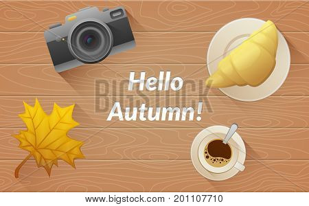 Hallo autumn text. Tasty buttery croissant and cup and camera of hot coffee on old wooden table with yellow leaves. Flat vector illustration