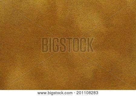 Background of golden purple suede fabric closeup. Velvet matt texture of orange nubuck textile.