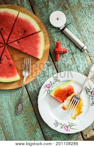 Fresh watermelon as vegan pizza with pizza knife and tire-bouchon on shabby wooden table above view