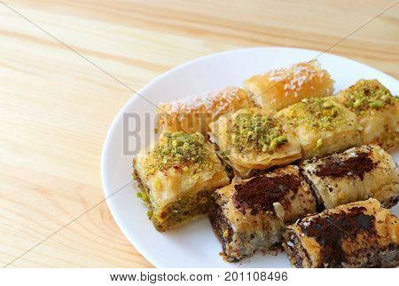 Many types of Baklava pastries on white plate served on wooden table, with free space for text and design