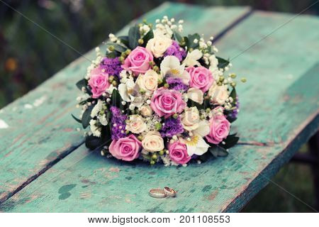 infinity sign of the rings wedding rings on a wood wedding bands wedding rings lie near bouquet of white and pink peach roses a bouquet of roses wedding flowers Selective focus