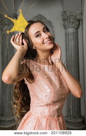 Pretty romantic lady with drawing crown. Beautiful young woman in a pink lacy dress in a vintage luxury grey interior. long curly hair fashion makeup