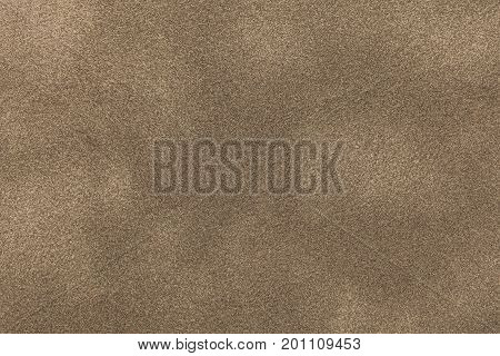 Background of light bronze suede fabric closeup. Velvet matt texture of sand nubuck textile.