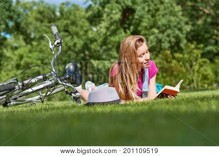 Young beautiful woman lying in the sun on the grass at the local park reading a book resting after riding bicycle lifestyle recreation holidays literature smart student learner concept.