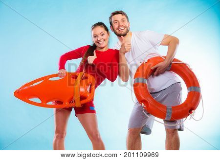 Accident prevention and water rescue. Young man and woman lifeguard couple on duty holding buoy lifesaver equipment on blue