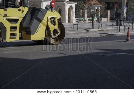Thessaloniki, Greece - August 23 2017: Steamroller presses asphalt at road. Yellow Road roller flattens asphalt at a road reconstruction site.