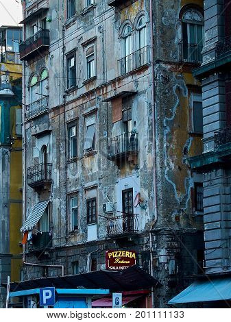Naples Italy - August 7 2017. Typical building of Naples with a pizzeria signboard at nightfall. Campania Italy.