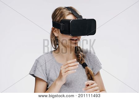 Beautiful young woman on a light background in virtual reality glasses.