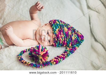 Newborn Baby In New Year's Gnome Cap Lays On A White Blanket
