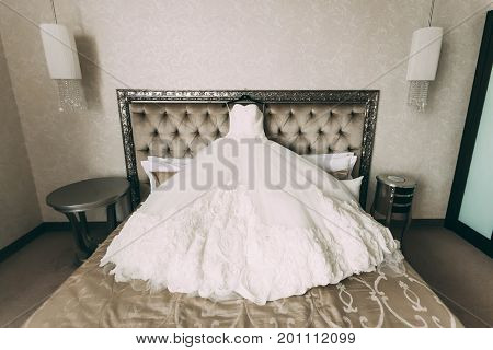 A Cream And Luxury Bridal Dress Which Lie On A Bed In Room. Artwork. Wide Angle