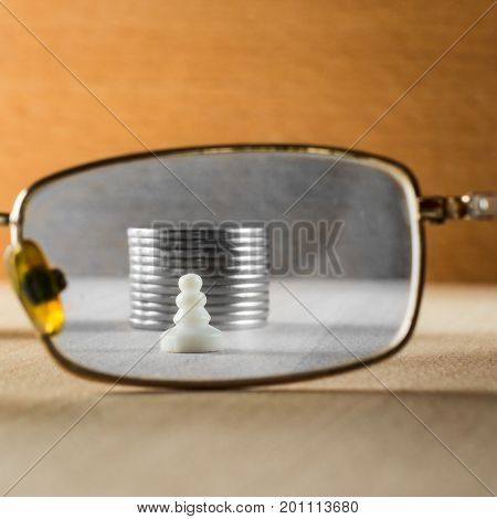 A chess pawn and coins behind a glass of eye glasses The concept of poverty and low earnings