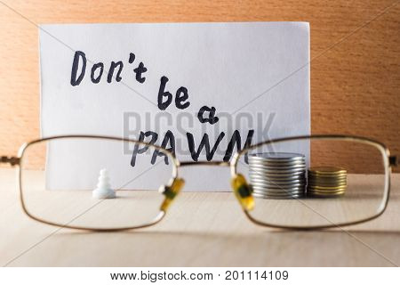 Do not be a pawn inscription in English near a pawn and coins on a wooden background