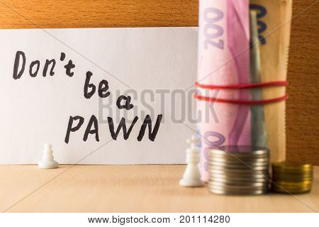 Pawn and king with money chess pieces symbolize people or enterprises of different statuses