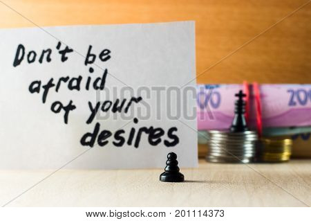 Pawn on the background of the king with money and motivating inscriptions in English do not be afraid of your desires