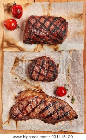 Gourmet Grill Restaurant Steak Menu - Various Grilled Beef Steak on Wooden Background. Black Angus Prime Beef Steak. Beef Steak Dinner. Top VIew