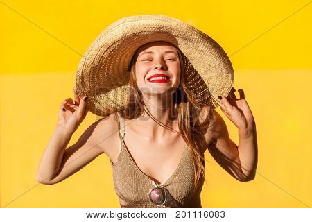 Good emotions and feelings. Close up. Portrait of beauty fashion model in straw hat. Looking at camera and toothy smile. Isolated on yellow background
