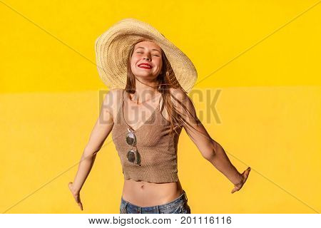 Portrait of cute young adult model in straw hat. Closed eyes and toothy smile. Isolated on yellow background