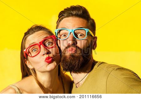 Portrait of young adult couple with color glasses. Freckled woman and bearded man send air kissing at camera. Studio shot