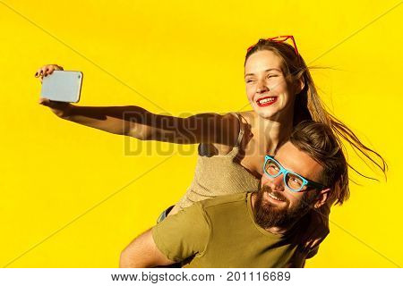 Happiness couple. Piggyback. Selfie. Hipsters couple macking selfie on yellow background. Studio shot