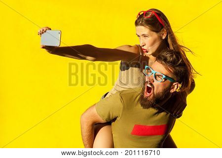 Piggyback. funny friends macking selfie on yellow background and grimacing . Studio shot