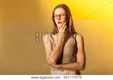 Hmm. Think about that. Young adult beautiful freckled woman touching her chin thinking and looking seriously at camera. isolated on yellow background studio shot
