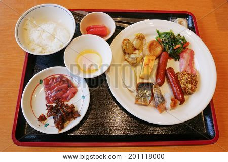 Buffet dinner food with onsen egg ferment squid salmon and scallop grilled sausage and bacon at hotel in Noboribetsu Japan