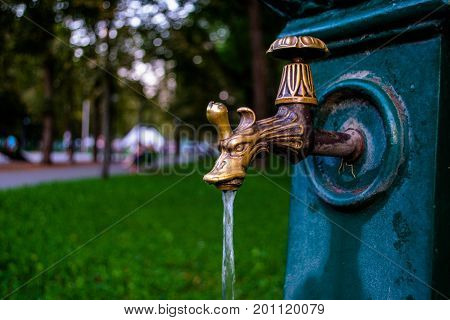Old rusty water tap in park. The flowing water on tap