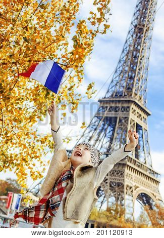 Child Rejoicing And Rising Flag While Sitting On Parapet, Paris