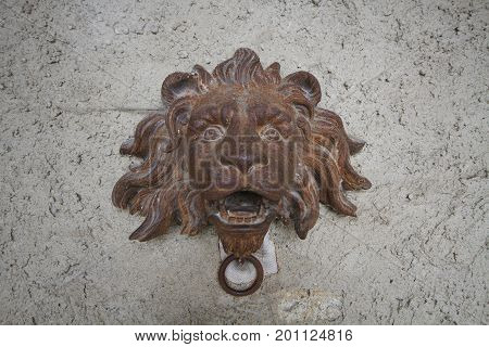 Wall brick stone sculpture with ancient rustic steel iron crafting of lion head statue, old historical door bell in castle of Europe, wallpaper, decoration, outdoor, backgrounds