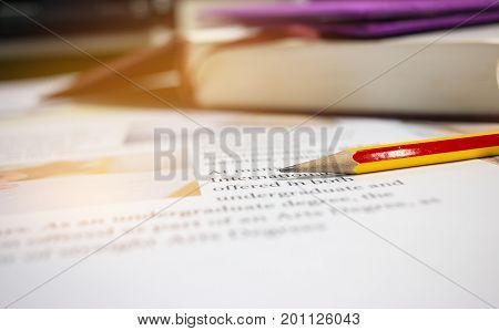 color pencil on letter-writing paper book with letter about postgraduate or undergraduate degree in college or school with image of of hands writing article near textbook concept of education