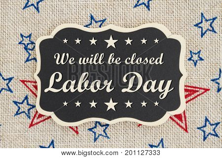 We will be closed Labor Day text on a chalkboard with patriotic USA red and blue stars on burlap