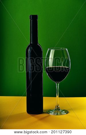 Wine In Glass And Bottle On Yellow Surface