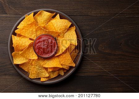 Mexican Snack Nachos Or Tortilla In Clay Plate With Dip Sauce On Rustic Wooden Background.
