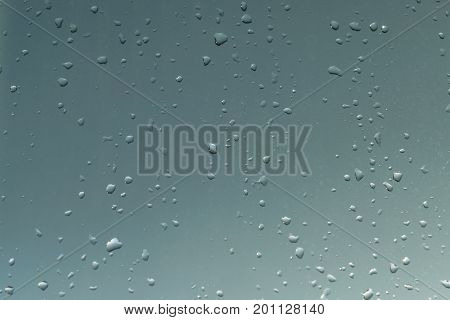 On the window a lot of different droplets from the rain. Behind the glass is visible on a background evening sky with clouds. Sunset. The window is in a small and large droplets from the rain.