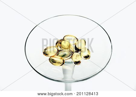 Capsules Of Cod-liver Oil On Glass Stem Isolated On White
