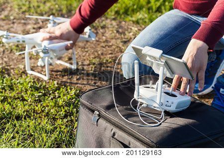quadcopter flights outdoors, aerial imagery and tech hobby concept - preparing to launch a drone on a summer lawn with green grass, male hands of pilot holding the quadrocopter and remote control