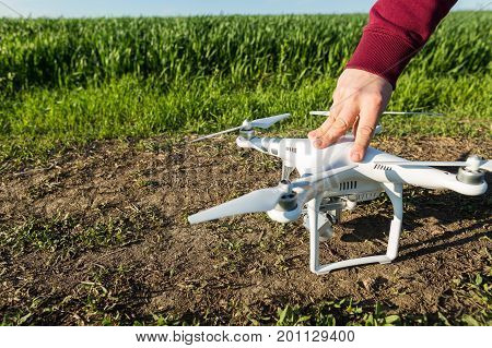 RUSSIA, ROSTOV-ON-DON - APRIL 20, 2017:- quadrocopter flight preparation on spring wheat field, male hand on the fuselage of the drone before takeoff