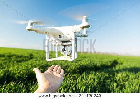 RUSSIA, ROSTOV-ON-DON - APRIL 20, 2017: closeup modern white high-tech copter flying at low altitude near male hand, background of blue sky and field of green grass