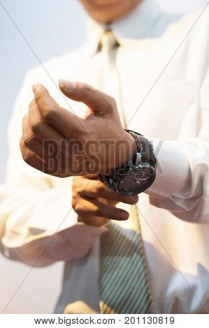The groom wears and adjust a wristwatch. The groom looks at his watch. Wedding detail preparation.