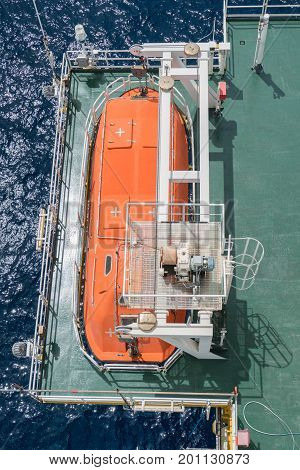 Life boat or survival craft at muster station of oil and gas accommodation platform for deploying when emergency.