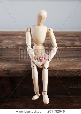 Wooden doll with heart in hands sitting on a wooden table. A dirty toy. Suffering from unhappy love