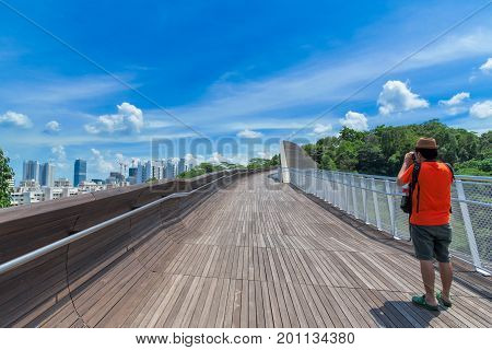Photographer or traveller using a professional DSLR camera take photo beautiful skyscraper at Singapore City View point from Henderson Wave Singapore