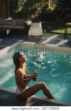 Young Woman By The Swimming Pool With Coctail