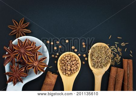 Star Anise and Spices coriander seeds, cumin seeds, cinnamon on black background with copy space