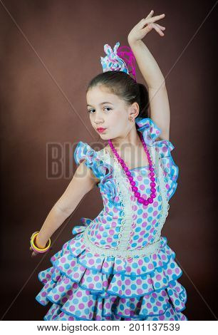 A sweet girl is dancing on a dark background. Spanish dance in a flamengo dress