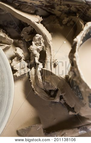 pottery, workshop, ceramics art concept - some fireclay and water around the Potter's wheel are reused as raw materials for new products, top view, close-up