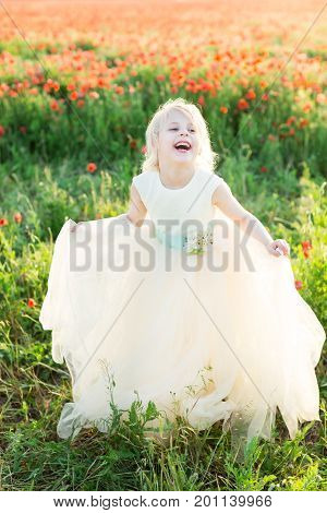 girl model, fashion, summer nature concept - young laughing girl, blonde model in field of poppies stands and holds hands of the edge wedding dress with a delicate blue sash decorated with flowers