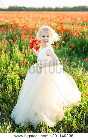girl model, poppies, wedding, fashion children, nature and summer concept - elegant girl bridesmaid with white hair, teases, shows the language, play in a field of poppies, she in white wedding dress