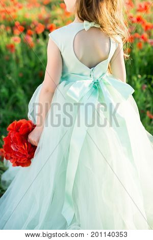 girl model, wedding, fashion concept - close-up on festive pale blue dress with cutout and bowknot on back of little girl bridesmaid with a bouquet of poppies in hand on the background of flower field